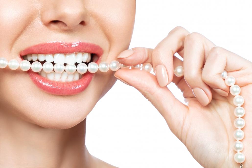 Mujer mostrando sus carillas dentales Lumineers mientras las compara con collar de perlas
